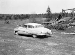 The Buick parked in front of the collapsed barn.