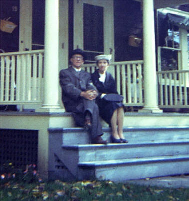 "Grampa and Gramma on the front ""stoop"" of their apartment at 19 Federal Street in St. Johnsbury."