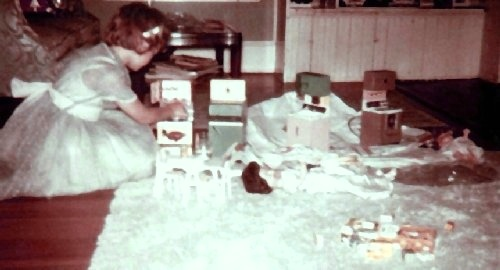 Mary Joan plays with her dolls in the living room.